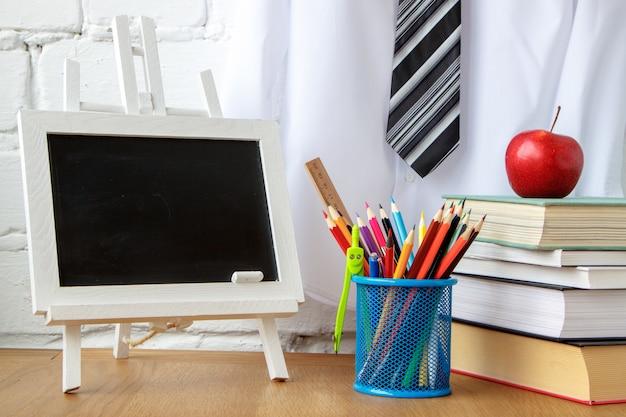 Material escolar, quadro de giz em miniatura, uma pilha de livros e uma maçã em cima da mesa Foto Premium