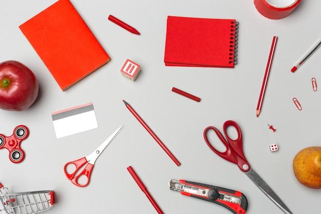 Material escolar vermelho no papel cinza Foto Premium