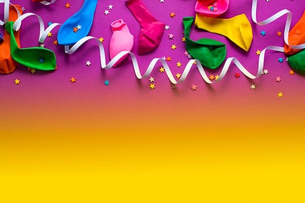 Material festivo roxo material colorido balões flâmulas confete Foto Premium