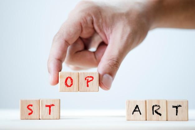 Matriz de mão humana iniciar e parar a palavra-chave em madeira cúbica Foto Premium