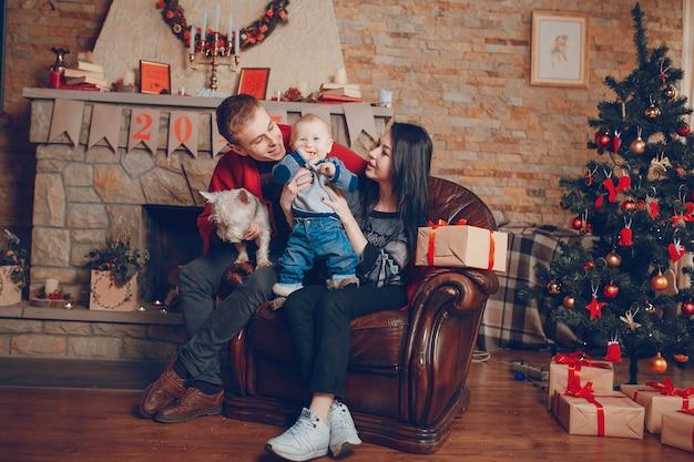 Matriz que levanta o bebê para cima, enquanto o pai prende o cão em joelhos Foto gratuita