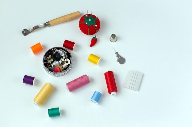 Meadas multicoloridas de linha, botões, agulhas - suprimentos de costura Foto Premium