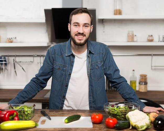 Meados de tiro homem sorrindo na cozinha Foto gratuita