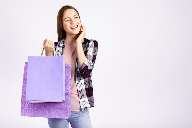 Meados de tiro mulher segurando sacos e desviar o olhar Foto gratuita