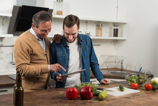 Meados de tiro pai e filho olhando para tablet na cozinha Foto gratuita