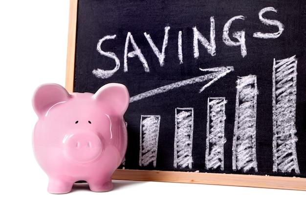 Mealheiro cor-de-rosa que está ao lado de um quadro-negro com carta de crescimento das economias. Foto Premium