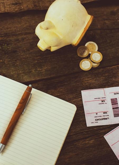 Mealheiro e bloco de notas na mesa de madeira Foto gratuita