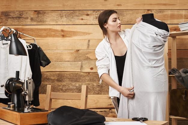 Meça duas vezes e corte uma vez. retrato do jovem designer caucasiano focado em vestuário, planejando um novo conceito de roupas no manequim, usando régua e tecido, querendo costurar um vestido novo na máquina de costura Foto gratuita