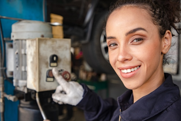 Mecânica de mulher bonita de uniforme está trabalhando no serviço automático com veículo levantado e botão de controle hidráulico. Foto Premium