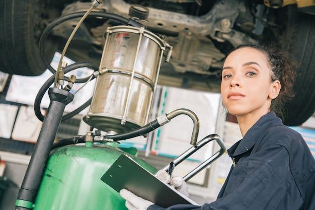 Mecânica de mulher bonita de uniforme está trabalhando no serviço automotivo com veículo elevado e relatórios em papel. Foto Premium