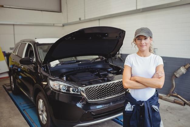 Mecânica em pé com os braços cruzados na frente do carro Foto gratuita