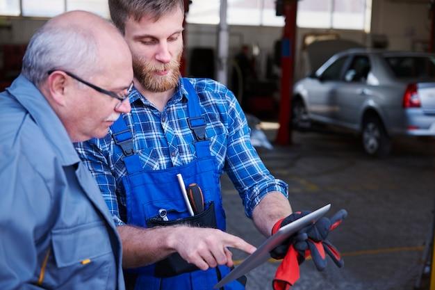 Mecânica verificando um planejamento em uma oficina Foto gratuita