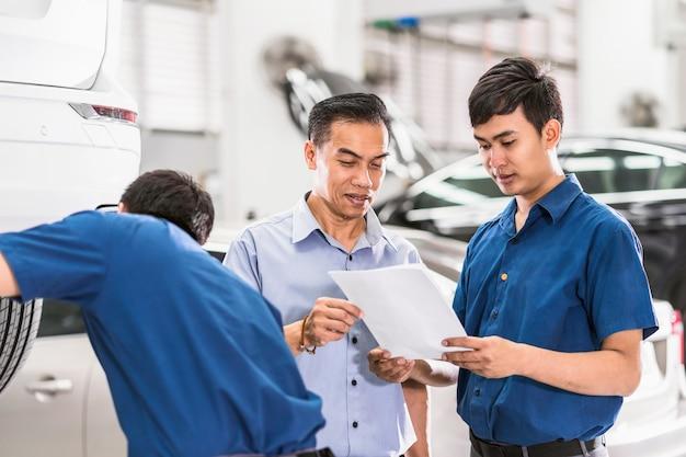 Mecânico asiático falando e mostrando trabalho ao cliente sobre o serviço de reparo no centro de serviços de manutenção Foto Premium
