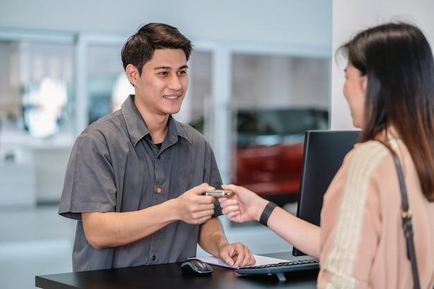 Mecânico asiático recebendo a chave do carro automático para verificação no centro de serviço de manutenção Foto Premium