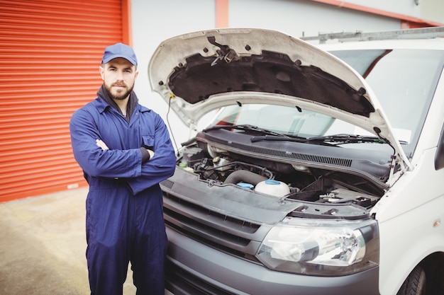 Mecânico com os braços cruzados em pé na frente de uma van Foto Premium