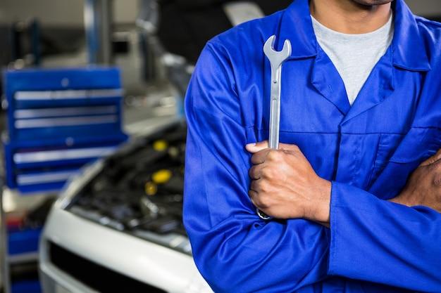 Mecânico com os braços cruzados segurando a chave inglesa Foto gratuita