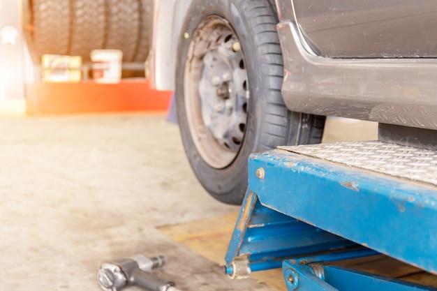 Mecânico consertando o dispositivo de alinhamento de roda em uma roda de carro de substituição de pneu novo Foto Premium