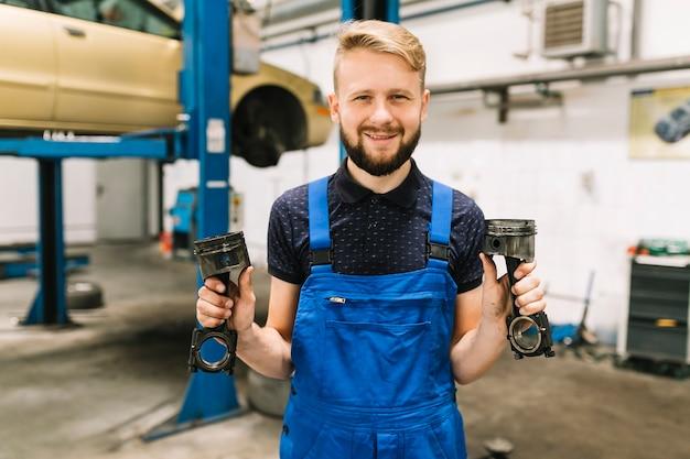Mecânico de automóveis em pistões de motor de manuseio uniforme Foto gratuita