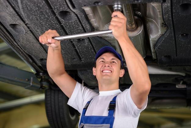 Mecânico de automóveis, examinando a suspensão do carro. Foto Premium