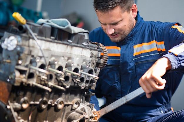 Mecânico de automóveis profissional reparando motor de automóvel usando uma chave inglesa na oficina Foto gratuita
