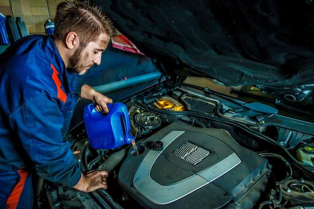 Mecânico de automóveis, substituindo e derramando óleo no motor na estação de serviço de reparo de manutenção. Foto Premium