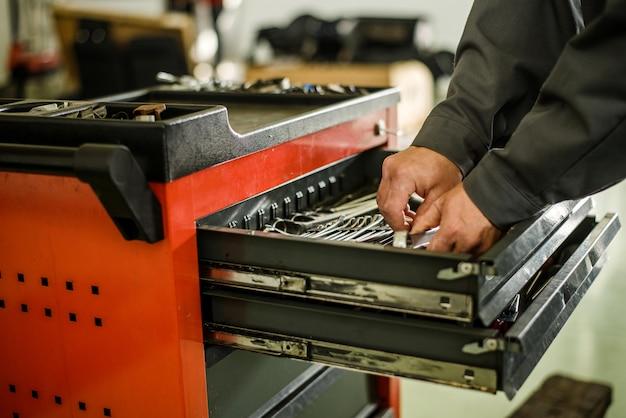 Mecânico de automóveis, tirando ferramentas da caixa de ferramentas. Foto Premium