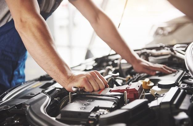 Mecânico de automóveis trabalhando em garagem. serviço de reparo. Foto gratuita