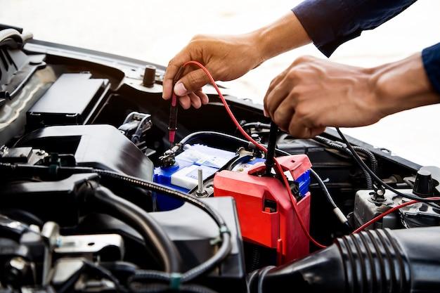 Mecânico de automóveis, usando o equipamento de medição para verificar a bateria do carro. Foto Premium