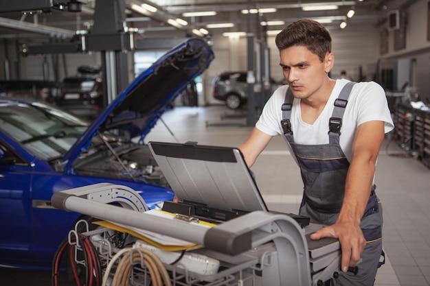 Mecânico de carro considerável novo que repara o veículo em sua garagem Foto Premium