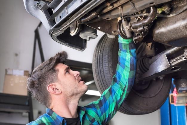 Mecânico de carro considerável que verifica o sistema de suspensão de um carro levantado na estação do serviço de reparações. Foto Premium