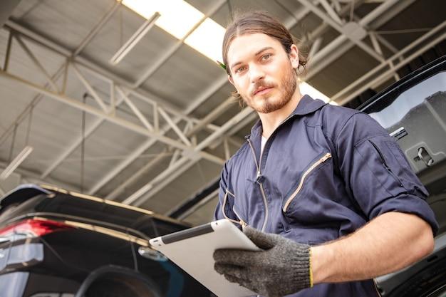 Mecânico de homem bonito de uniforme está trabalhando no serviço automotivo com veículo elevado e tablet. Foto Premium