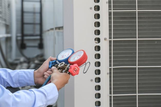 Mecânico de reparo do ar usando equipamento de medição para encher condicionadores de ar industriais de fábricas. Foto Premium