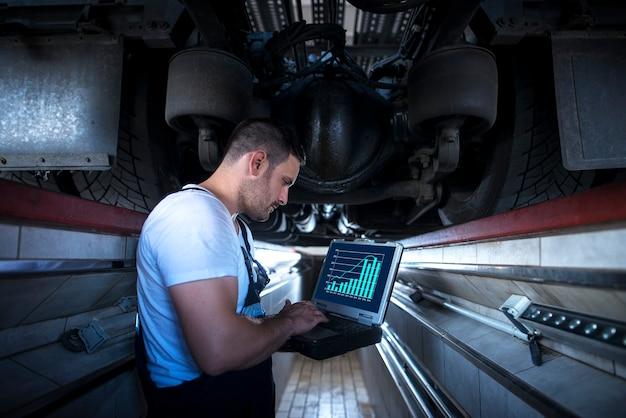 Mecânico de veículos com laptop de ferramenta de diagnóstico trabalhando sob o caminhão na oficina Foto gratuita