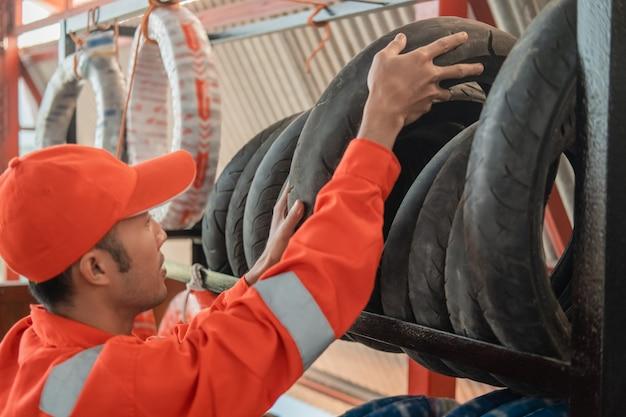 Mecânico em um uniforme de wearpack pega um pneu do rack em uma oficina de peças sobressalentes de motocicletas Foto Premium