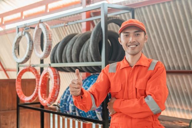 Mecânico em vermelho wearpack com polegares para cima enquanto na oficina com um suporte para pneus atrás Foto Premium