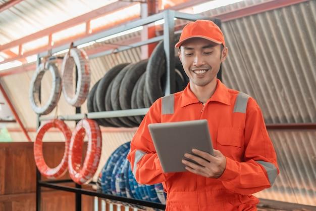 Mecânico em vermelho wearpack e chapéu usando uma almofada enquanto estiver na oficina com um suporte para pneus atrás Foto Premium
