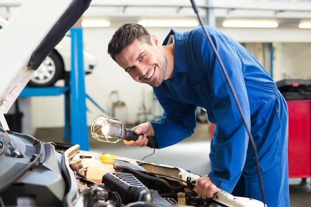 Mecânico examinando sob o capô do carro com tocha Foto Premium