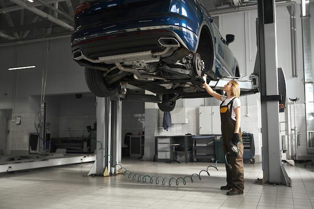 Mecânico fêmea observando o material rodante do carro levantado. Foto gratuita