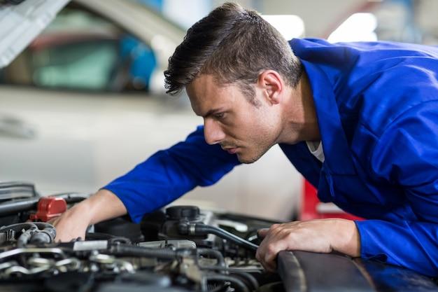 Mecânico manutenção de um motor de carro Foto gratuita