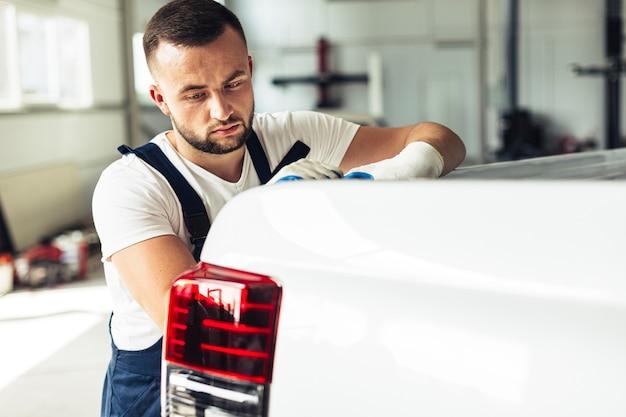 Mecânico masculino da vista lateral que verifica o carro para trás Foto gratuita