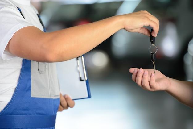 Mecânico masculino que dá chaves do carro ao cliente. Foto Premium