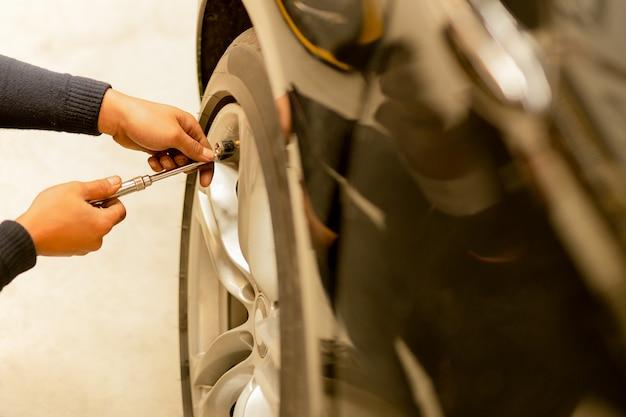 Mecânico que verifica a pressão de ar e que enche o ar nos pneus. Foto Premium