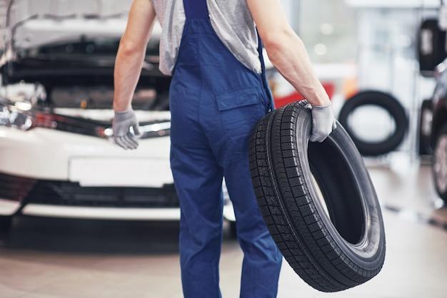 Mecânico segurando um pneu na garagem de reparação. substituição de pneus de inverno e verão Foto gratuita