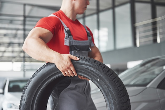 Mecânico segurando um pneu na oficina. substituição de pneus de inverno e verão. Foto gratuita