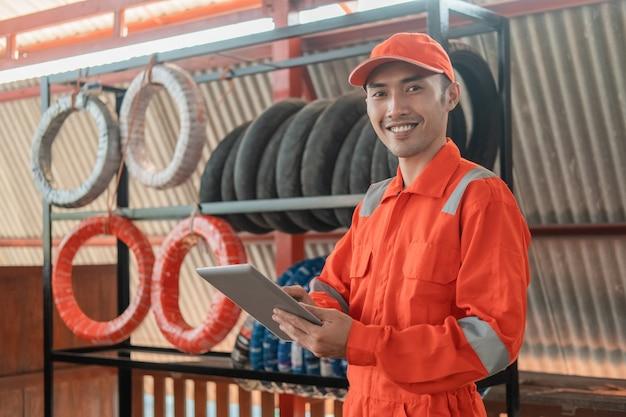 Mecânico sorridente no wearpack usando um tablet digital enquanto está na oficina com um suporte para pneus atrás Foto Premium