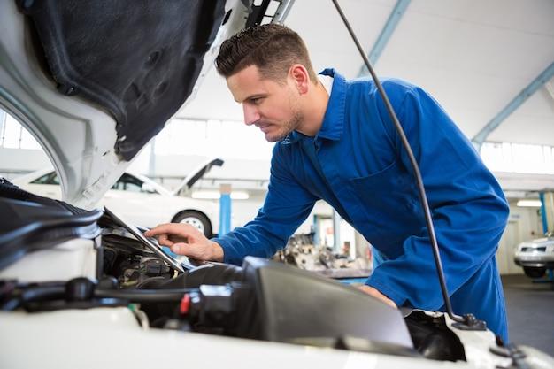 Mecânico usando tablet para consertar carro Foto Premium