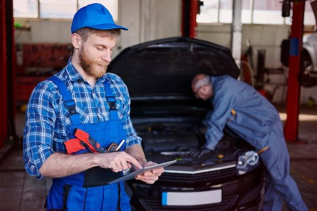 Mecânicos consertando um carro na oficina Foto gratuita