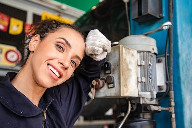 Mecânicos de mulher bonita de uniforme relaxando depois de trabalhar no serviço automático com veículo levantado e relatórios. Foto Premium