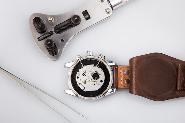 Mecanismo de relógio de pulso e ferramentas de reparo isoladas no branco Foto Premium