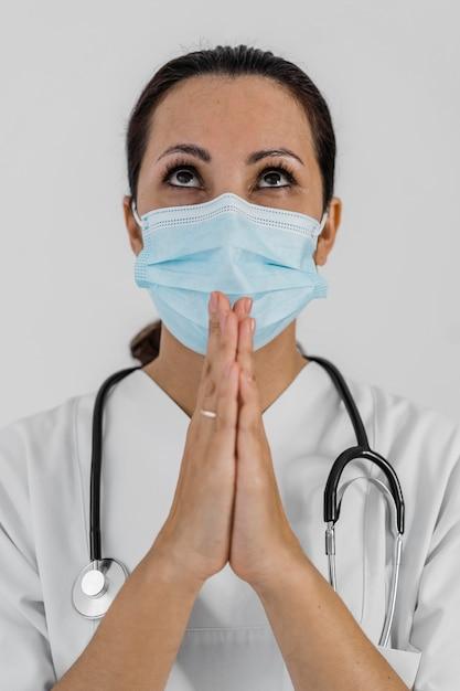 Médica com estetoscópio orando Foto gratuita